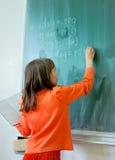 Scrittura della ragazza sulla scheda di banco Immagine Stock