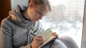Scrittura della ragazza in suo giornale mentre sedendosi ad una grande finestra. stock footage