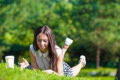 Scrittura della ragazza in suo taccuino fuori al parco Fotografie Stock