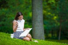 Scrittura della ragazza in suo taccuino fuori al parco Fotografia Stock Libera da Diritti