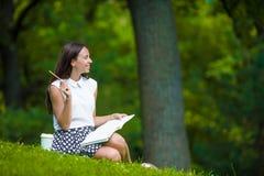 Scrittura della ragazza in suo taccuino fuori al parco Fotografie Stock Libere da Diritti