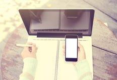 Scrittura della ragazza in un taccuino con un telefono cellulare e un computer portatile Immagine Stock Libera da Diritti