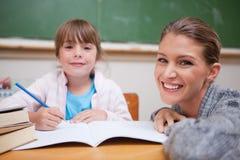 Scrittura della scolara con il suo insegnante Fotografie Stock