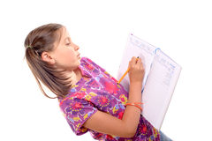 Scrittura della scolara nell'ordine del giorno Fotografia Stock