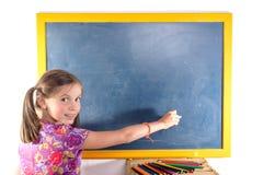 Scrittura della scolara su una lavagna Immagine Stock Libera da Diritti