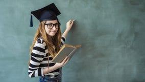 Scrittura della studentessa sulla lavagna verde fotografia stock libera da diritti