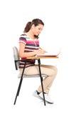 Scrittura della studentessa in un taccuino Fotografie Stock Libere da Diritti