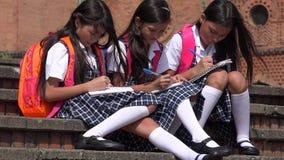 Scrittura delle studentesse colombiane giovani che portano gli uniformi scolastichi Fotografie Stock