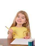 Scrittura dello scolaro allo scrittorio su bianco Fotografie Stock Libere da Diritti