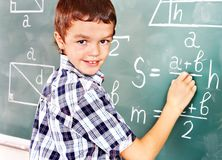 Scrittura dello scolaro sulla lavagna. Immagini Stock