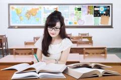 Scrittura dello studente della High School sul libro nella classe Fotografia Stock Libera da Diritti