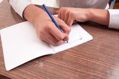 Scrittura dello studente dettaglio di una mano di scrittura del giovane su una nota Immagine Stock Libera da Diritti