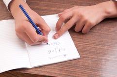 Scrittura dello studente dettaglio di una mano di scrittura del giovane su una nota Fotografia Stock