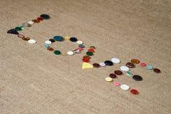 Scrittura di amore di parola con differenti bottoni di cucito Fotografie Stock
