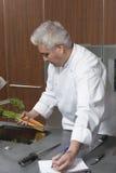 Scrittura di Holding Carrots And del cuoco unico in taccuino Fotografie Stock Libere da Diritti