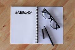 Scrittura di parola di assicurazione sul taccuino sulla tavola di legno Fotografie Stock