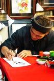 Scrittura di tiraggio del calligrafo in calligrafia. GOVERNO DELLA NIGERIA DI SAI, VIETNAM 1° FEBBRAIO 2013 Immagini Stock