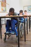 Scrittura disabile dell'allievo allo scrittorio in aula Immagine Stock