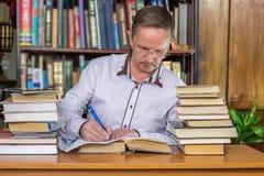 Scrittura e studiyng dell'uomo Immagine Stock