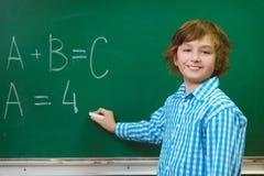 Scrittura felice del ragazzo sul fondo della lavagna Concetto della scuola ed educativo Fotografie Stock Libere da Diritti
