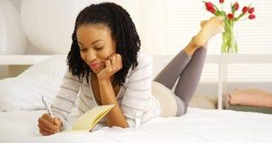 Scrittura felice della donna di colore in giornale Fotografie Stock Libere da Diritti