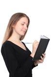 Scrittura felice della donna in un taccuino Fotografia Stock
