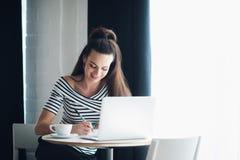 Scrittura felice della donna in un taccuino ed in un sorridere Femmina adulta che si siede alla tavola con un computer portatile  Immagine Stock