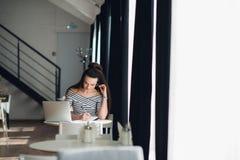 Scrittura felice della donna in un taccuino Femmina adulta che si siede alla tavola vicino alla finestra con un computer portatil Immagini Stock