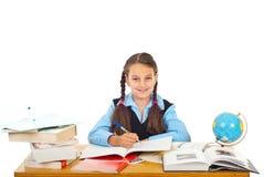 Scrittura felice della scolara alla pupilla Fotografia Stock Libera da Diritti