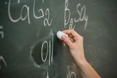Scrittura femminile abbastanza giovane dello studente di college sulla lavagna della lavagna durante la classe di chimica Immagini Stock Libere da Diritti