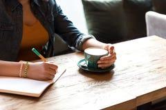 Scrittura femminile del braccio nel quaderno alla tavola Fotografia Stock