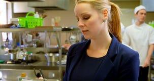 Scrittura femminile del responsabile sulla lavagna per appunti in cucina 4k stock footage