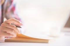 Scrittura femminile della mano in blocco note Immagine Stock