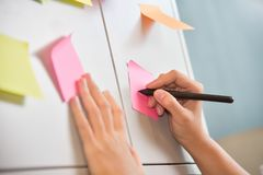 Scrittura femminile della mano sulle note di Post-it Immagini Stock Libere da Diritti