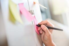 Scrittura femminile della mano sulle note di Post-it Immagine Stock Libera da Diritti