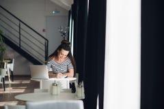 Scrittura femminile sorridente qualcosa in suo taccuino mentre sedendosi ad uno scrittorio con un computer portatile Fotografia Stock