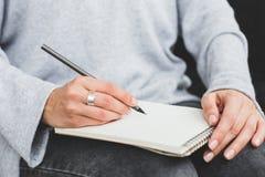 Scrittura femminile in taccuino, fine della mano su Immagine Stock