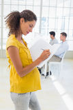 Scrittura incinta casuale della donna di affari nella cartella Immagini Stock