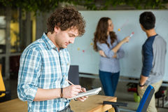 Scrittura maschio concentrata in taccuino e workinng con i partner Immagini Stock