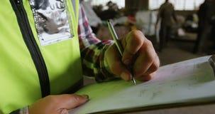 Scrittura maschio del lavoratore sulla lavagna per appunti in magazzino 4k stock footage