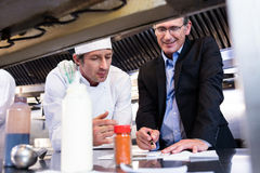 Scrittura maschio del responsabile del ristorante sulla lavagna per appunti mentre interagendo al cuoco unico capo Fotografia Stock