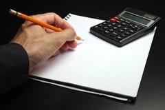 Scrittura maschio della mano su un blocchetto per appunti Immagine Stock