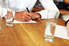Scrittura maschio della mano su un documento Fotografia Stock