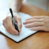 Scrittura maschio della mano su un taccuino Fotografie Stock