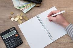 Scrittura maschio della mano in una penna stilografica del diario di affari con il calcolatore, euro Fotografie Stock