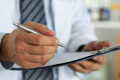 Scrittura maschio della penna dell'argento della tenuta della mano di medico della medicina Immagini Stock