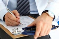 Scrittura maschio della penna dell'argento della tenuta della mano di medico della medicina Fotografie Stock Libere da Diritti