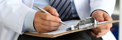 Scrittura maschio della penna dell'argento della tenuta della mano di medico della medicina Fotografie Stock