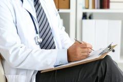 Scrittura maschio della penna dell'argento della tenuta della mano di medico della medicina Fotografia Stock Libera da Diritti