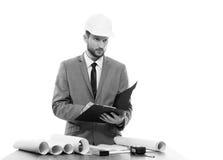 Scrittura maschio professionale del constructionist sulla sua lavagna per appunti fotografia stock